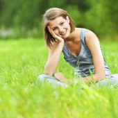 woman sitting on green meadow with her legs crossed