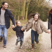 Family Running On Winter Countryside Walk Together