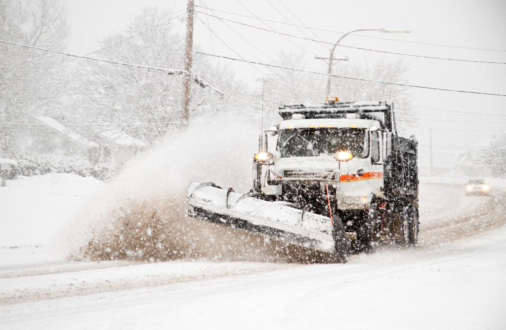 dumptruck with plow plowing snow during northeaster