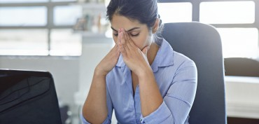 Shot of a businesswoman experiencing stress at work
