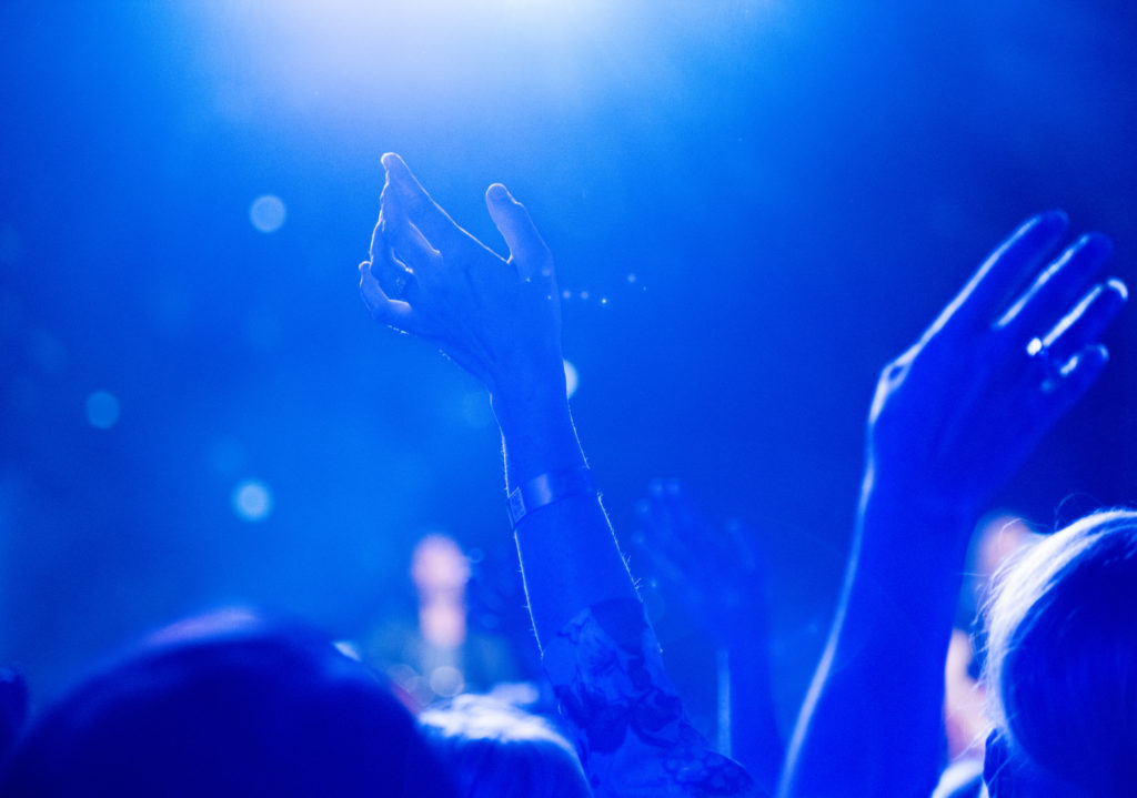 Hands raise at concert with ambient blue light haze