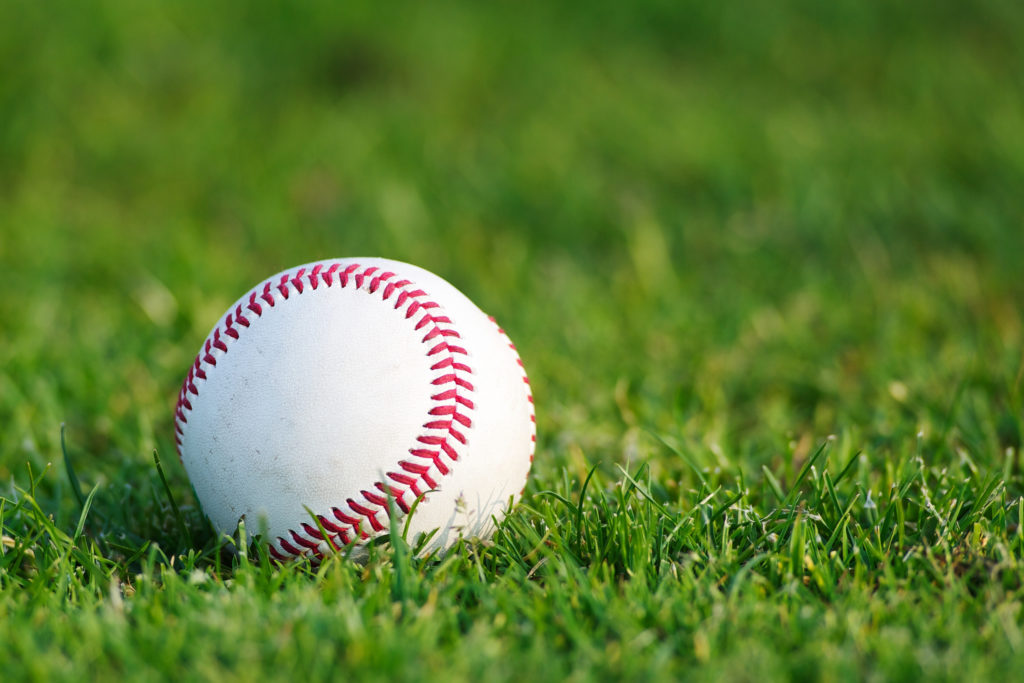 White used baseball on the green grass close-up as macro shot with copy space on the right and top