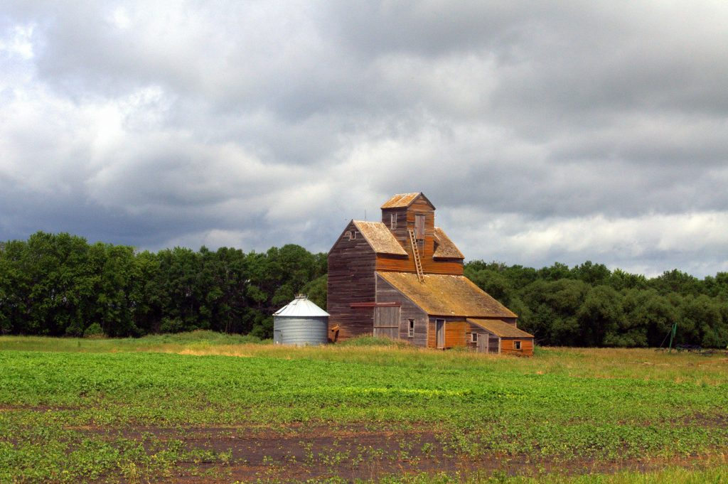Old barn, with cloudy sky, in the middle of an open field in North Dakota.
