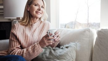 Shot of a mature woman relaxing on the sofa at home with a cup of coffee