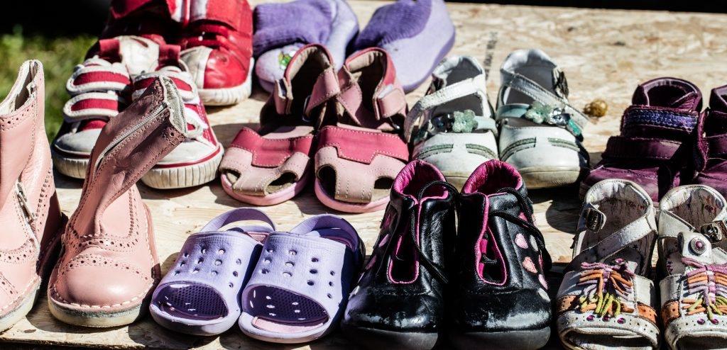display of used child and baby girl shoes for reusing,reselling,charity,donating or thrift store for second life sold at flea market at springtime