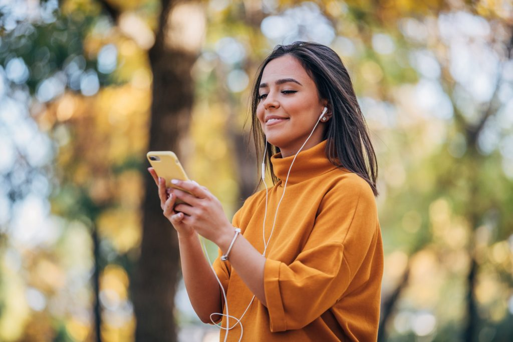One woman, beautiful young woman in park, using smart phone, listening music on headphones.