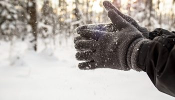 A man playfully shakes off snowflakes from gloves, after winter fun, against the background of snow-covered forest and the bright sun.